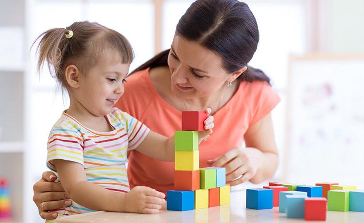 Une assistante maternelle accueille une petite fille